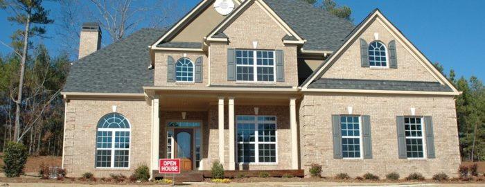 """Large two-story home with an """"open house"""" sign out front"""