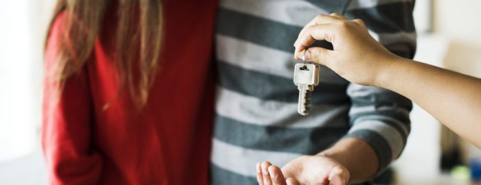 Young couple accepting the keys to their new home.