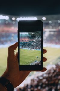 A person taking a photo of a soccer game.