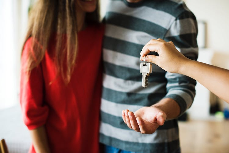 First-time home buyers being handed the keys to their new home.